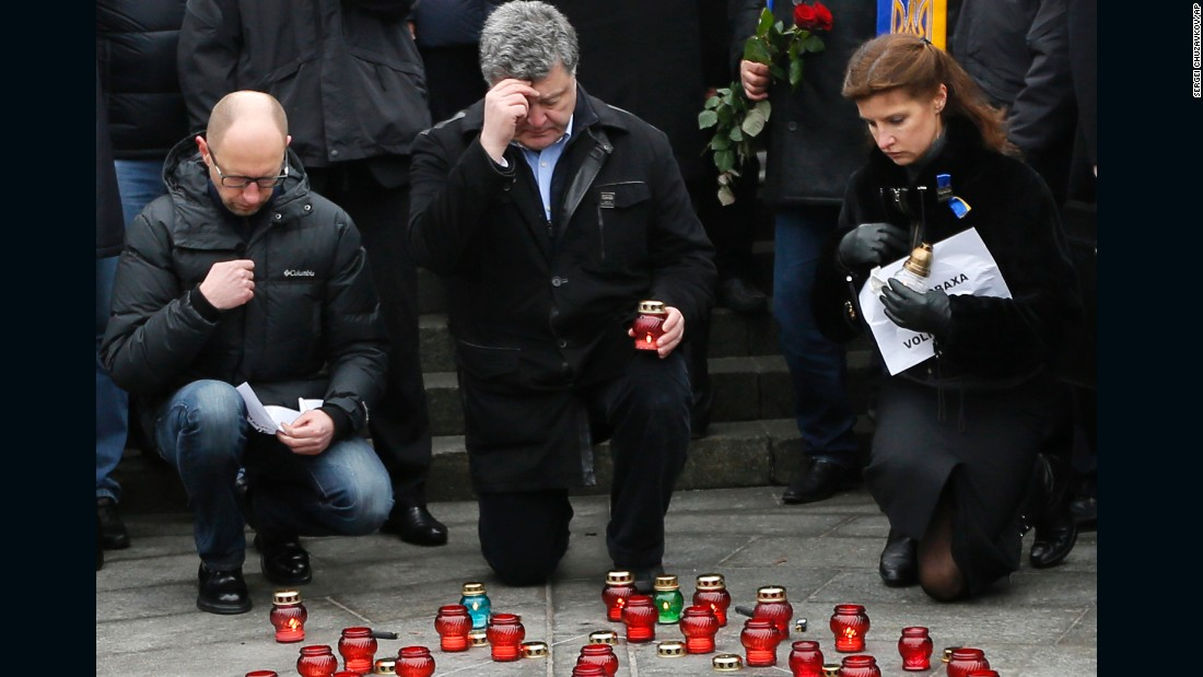Ukrainian President Petro Poroshenko, center, his wife Maria and Ukrainian Prime Minister Arseniy Yatsenyuk pay their respects during a rally on Sunday, January 18, at Independence Square in Kiev, Ukraine. The rally was to show solidarity with the victims of a rocket attack that claimed 13 lives on a highway near the town of Volnovakha.