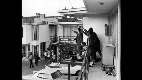 Dr. Ralph Abernathy, Jesse Jackson and others stand on the balcony of the Lorraine Motel in Memphis, Tennessee, on April 4, 1968, pointing in the direction of the gunshots that killed King, who lies at their feet.