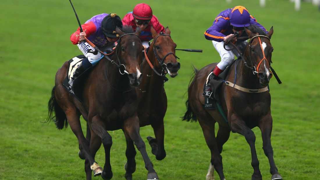 Moore (left) has regularly ridden in the Queen's colors such as here en route to winning The Gold Cup at Royal Ascot on board Estimate.