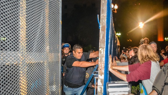 "The mood changed from calm to anger as the night fell Monday. ""As the sun started setting, the mood noticeably changed as people started charging the fence protecting Casa Rosada,"" said freelance photographer Jerry Nelson. The Casa Rosada is the presidential quarters."