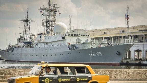 A Soviet-made Lada limousine passes by the Russian warship CCB-175 Viktor Leonov docked in 2014 in Havana.