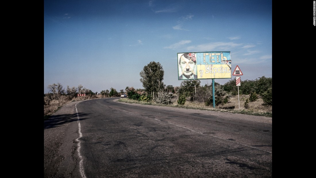"A billboard with a picture of Russian President Vladimir Putin as Hitler and the words ""Get out from Ukraine,"" is seen on the road from Mykolaiv to Kherson in July 2014."