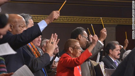 U.S. lawmakers pay tribute to the victims of the Paris terrorist attacks by holding up pencils during President Barack Obama's State of the Union address.
