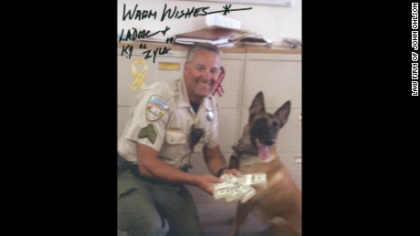 Sheriff Lee Dove autographed photos of himself with a bundle of money.