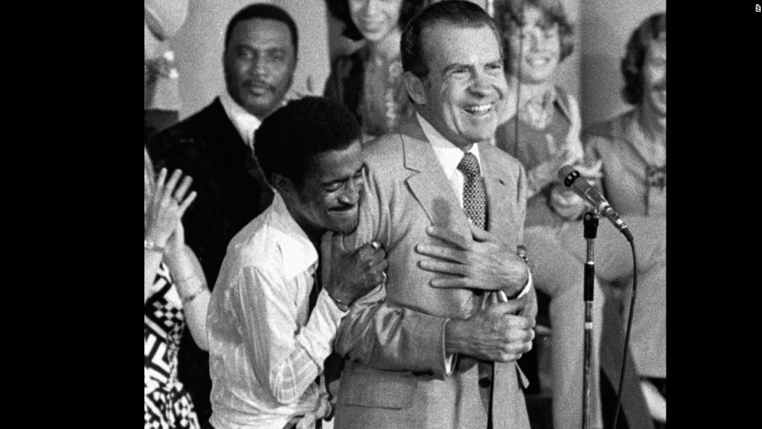 "Entertainer Sammy Davis Jr. hugs President Richard Nixon from behind as Nixon addresses supporters at a youth rally in Miami, Florida, on August 22, 1972. ""Davis faced ostracism from former friends who accused him of 'selling out' when he hugged Nixon,"" according to the <a href=""Davis faced ostracism from former friends who accused him of ""selling out"" when he hugged Nixon at a televised youth rally during the 1972 Republican National Convention."" target=""_blank"">Library of Congress</a>."