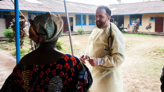 Dr. Rick Sacra visits with a woman at one of the health clinic where he works in Liberia.