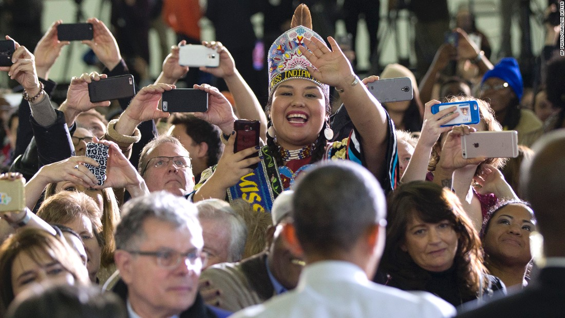 "JANUARY 22 - BOISE, IDAHO: A woman dressed in Native American dress waves as U.S. President Barack Obama greets people in the audience at Boise State University. Obama gave a speech about the themes of his <a href=""http://cnn.com/2015/01/20/politics/state-of-the-union-address-2015-preview/"">State of the Union address. </a>"