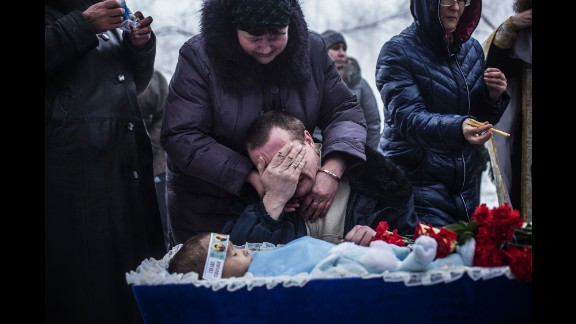 Vladimir Bovrichev cries next to the body of his 4-year-old son, Artiam, during Artiam
