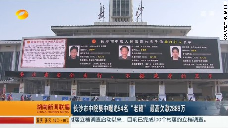 "This screen grab from Chinese state television shows the billboard outside Changsha railway station and reads that the court is outing a list of ""dishonest persons."""