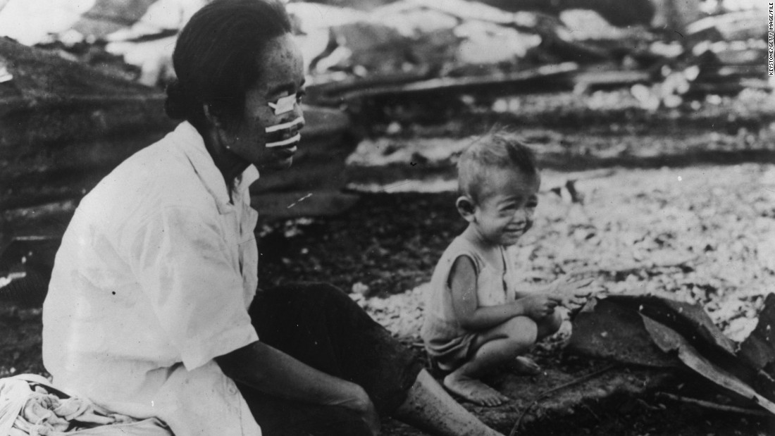 A Filipina woman wounded in the face by shrapnel waits in front of her burnt home in Manila in March 1945. An estimated million Filipino civilians died during World War II.