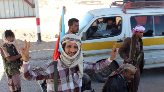Supporters of the separatist Southern Movement flash the victory sign after they seized police security checkpoints on Saturday, January 24, in Ataq, the capital of the Shabwa province in Yemen. Policemen were told to give up their weapons and return to their bases before the militiamen raised flags of the formerly independent South Yemen at the checkpoints.