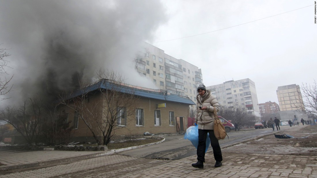 A resident walks by a burning building in Mariupol on Saturday, January 24.