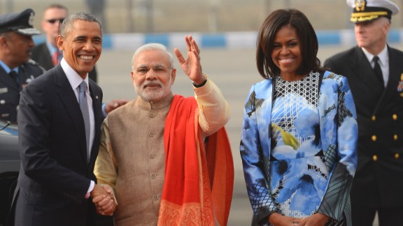 Obama shakes hands with Modi as first lady Michelle Obama stands beside them upon arrival at the Palam Air Force Station in New Delhi.