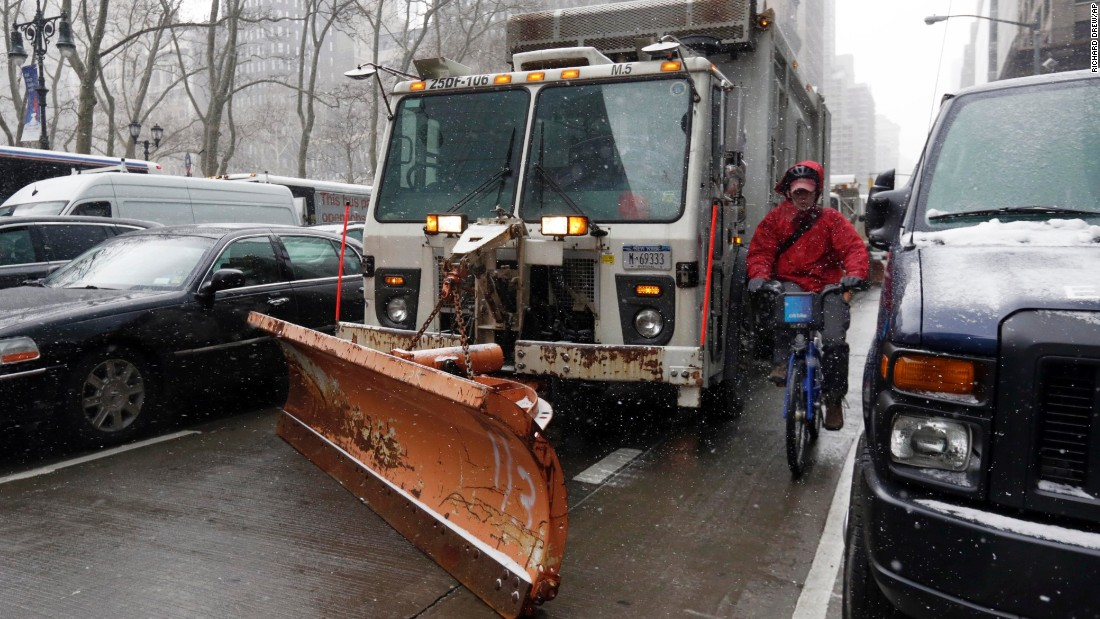 A cyclist in New York navigates between parked cars and a sanitation truck with a snow plow on it on January 26.