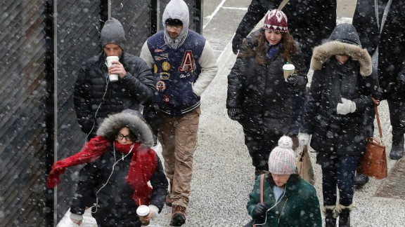 Snow falls on pedestrians in New York on January 26.