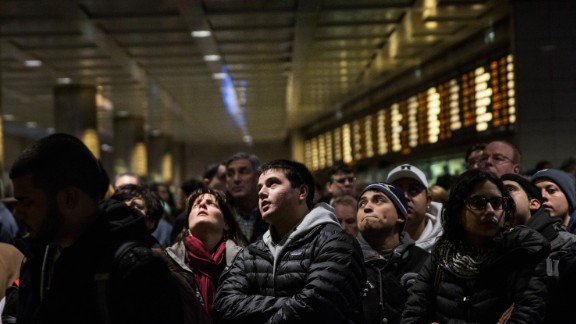 Travelers wait for their train platform to be announced at New York's Penn Station on January 26.