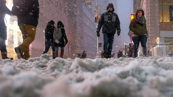 People cross a street covered in snow in New York