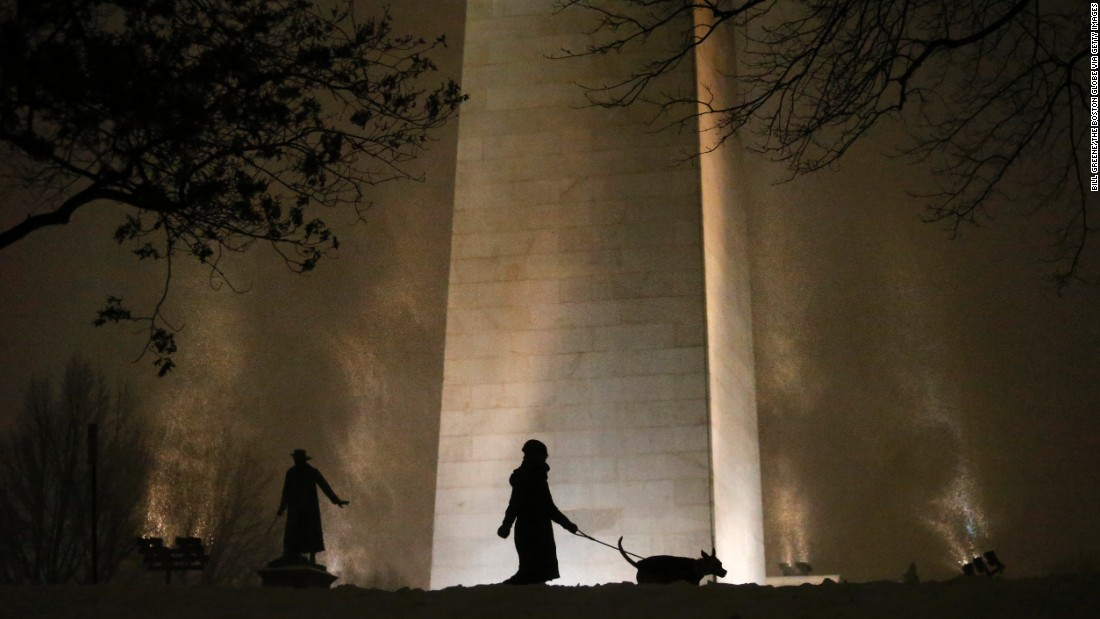 A woman walks her dog as snow swirls around the Bunker Hill Monument in Boston on Monday, January 26.