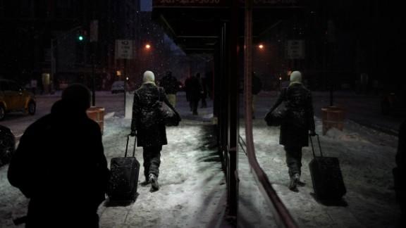 People walk through falling snow in Hoboken, New Jersey, on January 26.