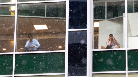 People look out from office building windows as snow falls in downtown Philadelphia on January 26.