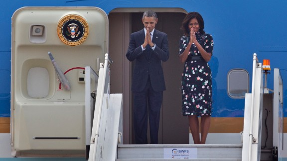 U.S. President Barack Obama and first lady Michelle Obama fold their hands together in a traditional Indian greeting gesture as they prepare to board Air Force One to depart New Delhi on Tuesday, January 27.