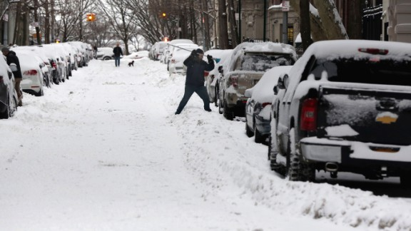 A man clears his snow-covered car on the Upper West Side in New York City on January 27.
