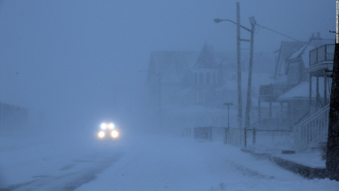 An emergency vehicle drives down a snowy street in Winthrop, Massachusetts, on January 27.