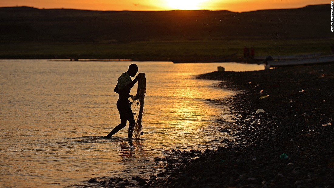 A fisherman from the El Molo tribe walks ashore as the sun rises over Komote, a village on the banks of Lake Turkana, Kenya, near the location of the new wind farm.