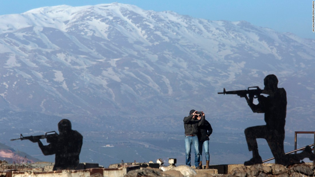 A couple enjoys the view as they take selfies between soldier cutouts Friday, January 23, at the Merom Golan lookout position in the Golan Heights. The tourist site has a sweeping view of the Quneitra area of Syria.