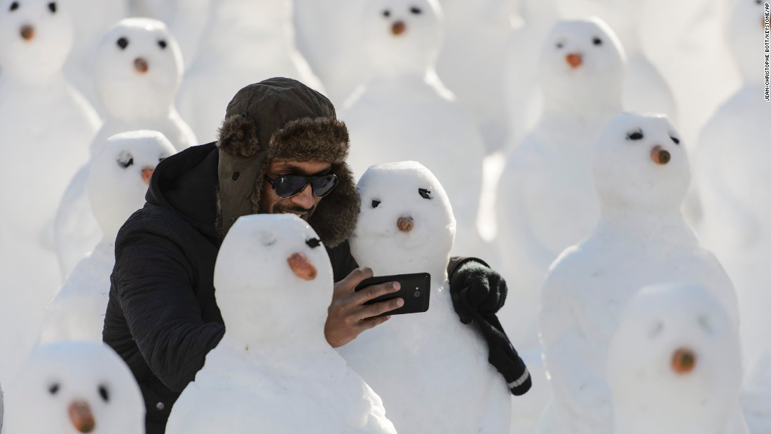 A man takes a photo with snowmen Saturday, January 24, during a protest against the World Economic Forum in Davos, Switzerland.