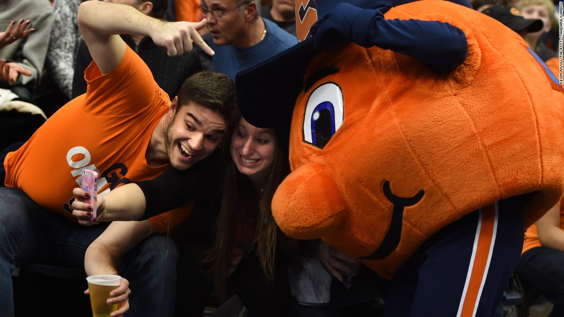 Two Syracuse fans get a shot with Otto the Orange during a college basketball game Friday, January 24, in Syracuse, New York.
