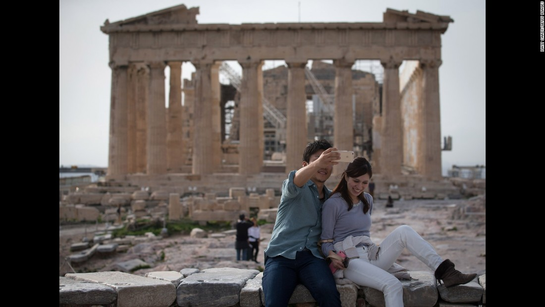 A couple takes a photo in front of the Acropolis in Athens, Greece, on Thursday, January 22.