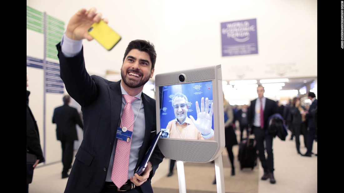 An employee takes a selfie with a Beam robot, a remote presence system made by Suitable Technologies, during the World Economic Forum on Friday, January 23. The forum's annual meeting took place last week in Davos, Switzerland.
