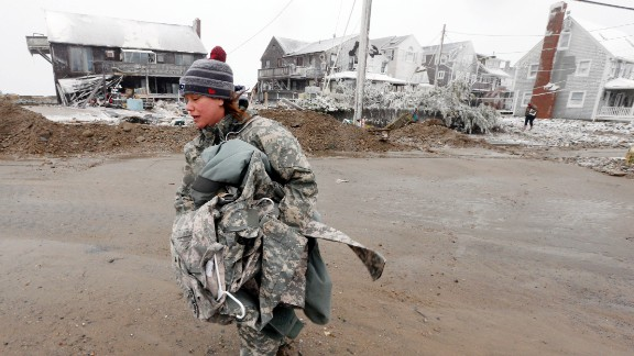 U.S. Army soldier Jennifer Bruno carries belongings from her house, center rear, which was heavily damaged by storm surge in Marshfield, Massachusetts.
