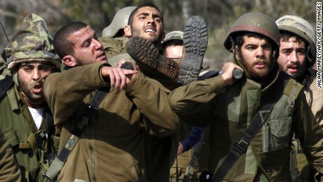 Israeli soldiers carry an injured soldier in an occupied area along the Israel-Lebanon border on Wednesday.