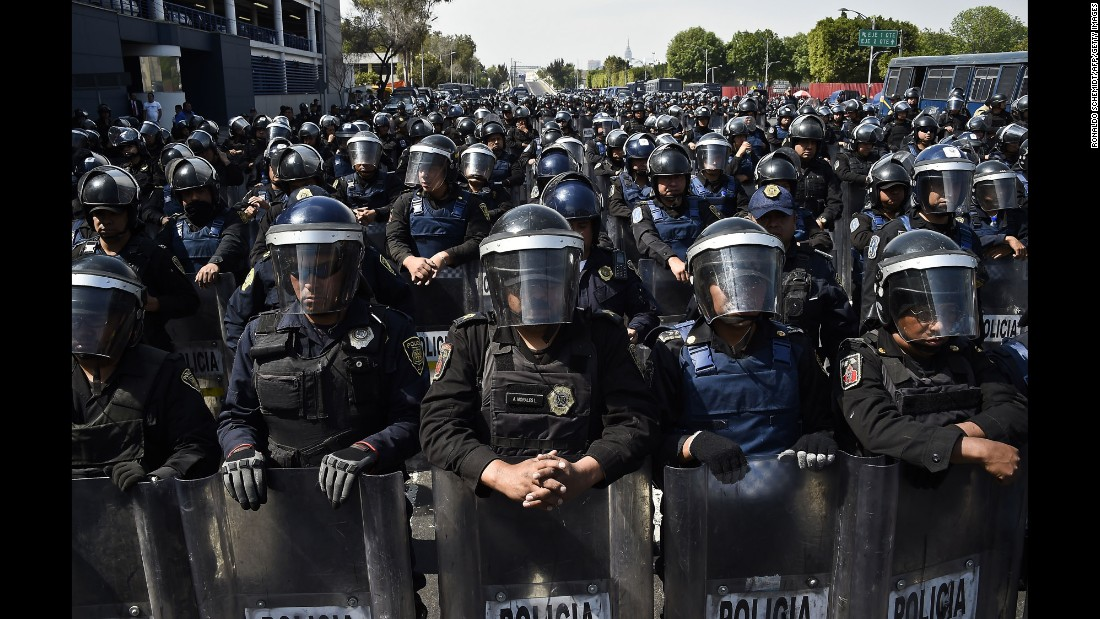 Hundreds of police officers in riot gear block a street during several marches in Mexico City on January 26.