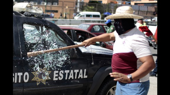 A man smashes the window of a traffic patrol vehicle during a protest in Chilpancingo, Mexico, on Thursday, January 15.