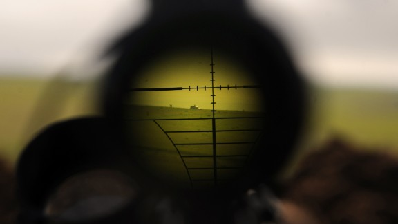 ISIS militants are seen through a rifle