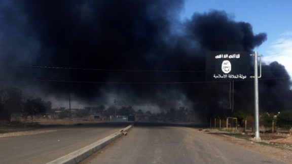 Smoke billows behind an ISIS sign during an Iraqi military operation to regain control of the town of Sadiyah, about 95 kilometers (60 miles) north of Baghdad, on Tuesday, November 25.
