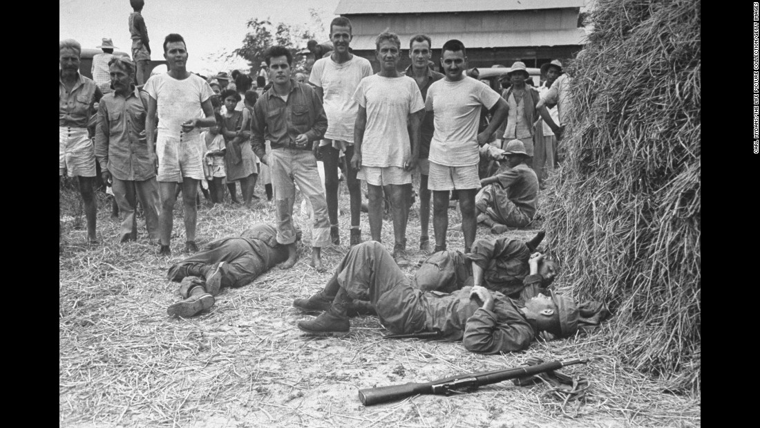Exhausted Army Rangers sleep on straw-covered ground in front of some of the POWs they rescued.