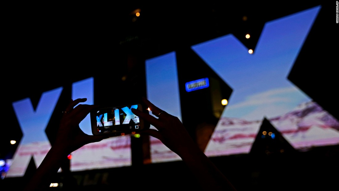 A woman takes a photo of Roman numerals for Super Bowl XLIX Wednesday, Jan. 28, 2015, in downtown Phoenix. The New England Patriots face the Seattle Seahawks in Super Bowl XLIX on Sunday in Glendale, Ariz. (AP Photo/Charlie Riedel)