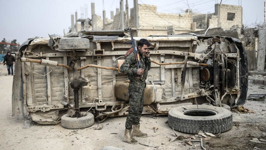"A Kurdish fighter talks on the phone in Kobani, Syria, a couple days after it was recaptured from ISIS on Monday, January 26. Kobani, also known as Ayn al-Arab, had been <a href=""http://www.cnn.com/2014/06/13/world/gallery/iraq-under-siege/index.html"" target=""_blank"">under assault by ISIS</a> since mid-September."