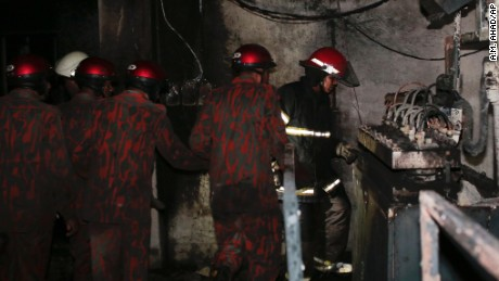 Firefighters inspect the damage inside a scorched plastic factory Saturday in Dhaka, Bangladesh.
