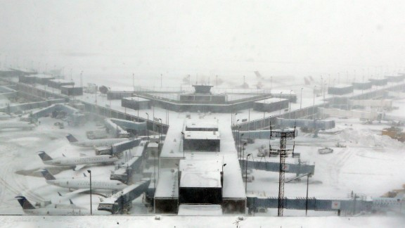 Airplanes stand in the snow at O'Hare International Airport on Sunday, Feb. 1, 2015, in Chicago. A slow-moving winter storm blanketed a large swath of the Plains and Midwest in snow Sunday, forcing the cancellation of more than 1,500 flights, making roads treacherous and forcing some people to rethink their plans to attend Super Bowl parties. (AP Photo/Nam Y. Huh)