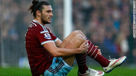 Andy Carroll of West Ham United grimaces as he hits the turf in a Premier League game against Arsenal in 2014.
