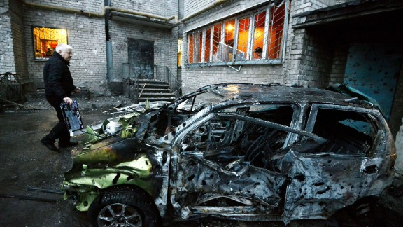 A man stands next to his car in Donetsk on Sunday, Febuary 1, after it was destroyed by shelling.