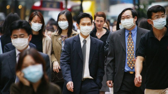 In 2003, Severe Acute Respiratory Syndrome (SARS) became a global pandemic, infecting over 8,000 people worldwide and causing the death of 774. Pictured, people wear surgical masks to try to reduce the chance of infection from SARS whilst walking through the business district April 1, 2003 in Hong Kong.