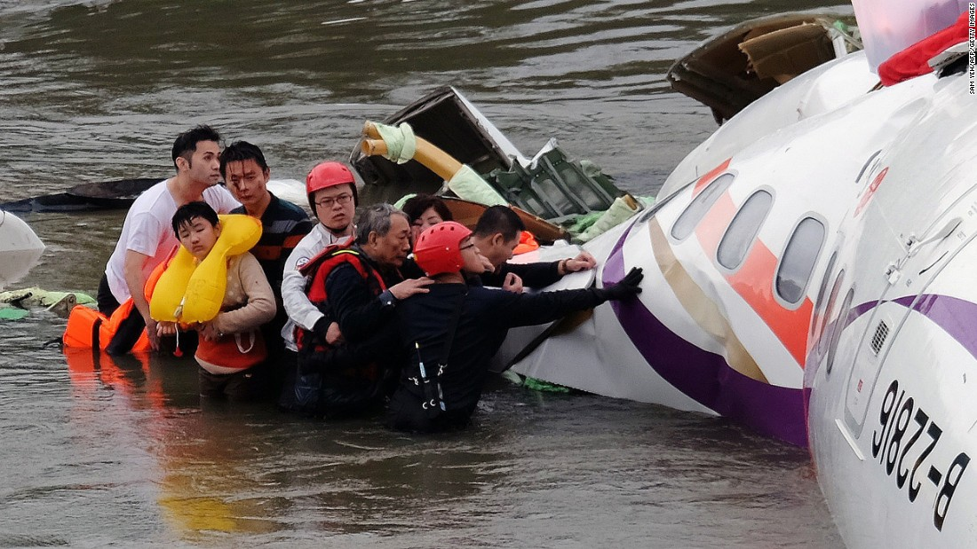 Rescue personnel assist passengers as they wait to be transported to land on February 4.