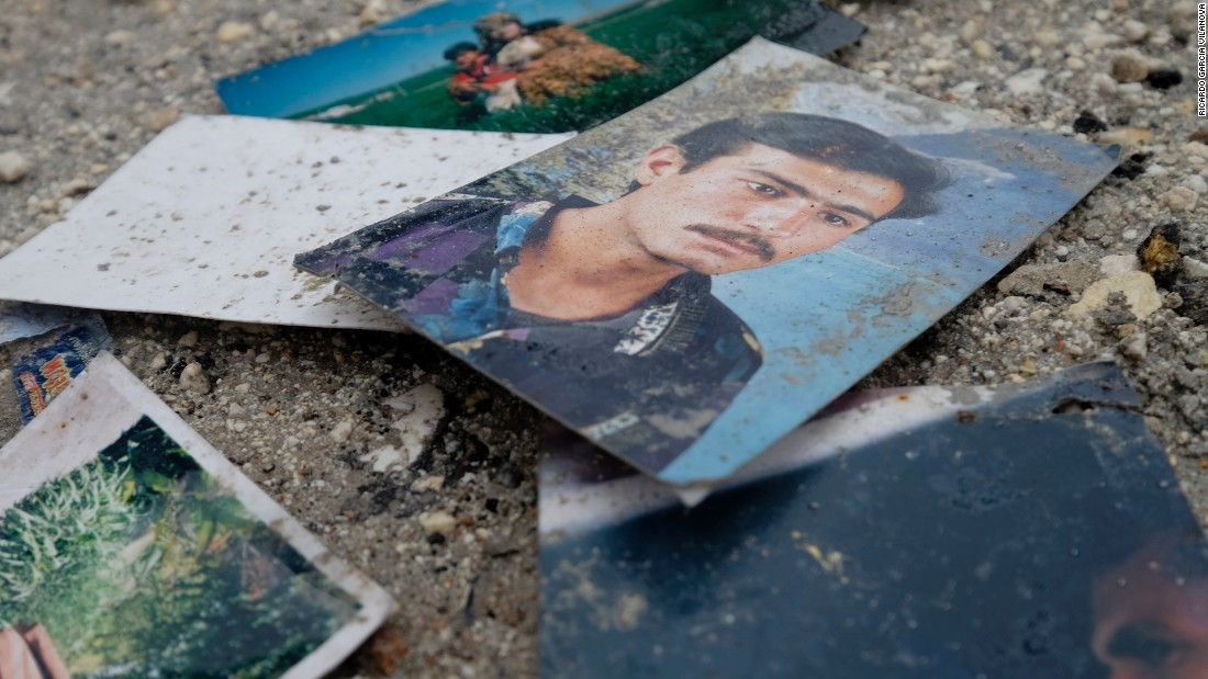 Photographs of civilians are seen on a street outside of a destroyed house on Saturday, January 31.