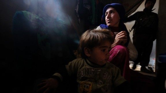 Zehra, a 25-year-old Kurdish woman who lost her 8-month-old daughter due to a lung infection at a refugee camp, sits with her other daughter inside their home in Kobani, Syria, on Thursday, January 29. Her husband, a fighter from the People